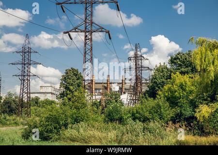 Stromleitungen unter grünen Gras gegen den blauen Himmel - Stockfoto
