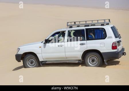 Eine Gruppe von Touristen in weißen Geländewagen durch endlose Sand der Wüste Sahara in Tunesien fahren - Stockfoto