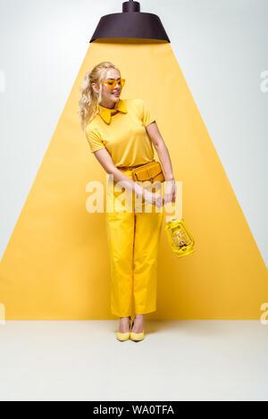 Gerne blonde Frau in Sonnenbrille posing und Holding vintage Lampe auf Weiß und Gelb - Stockfoto