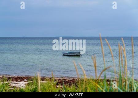Kleines Boot driftet im Wasser an der Küste mit einem weiten Blick über die Ostsee. - Stockfoto
