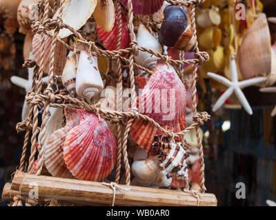 Traditionelle bunte home Dekorationen aus verschiedenen Formen und Farben seashells gemacht. Souvenir Umhang auf der tropischen Sea Resort Markt - Stockfoto