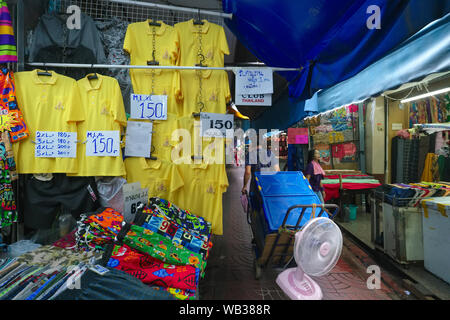 Den gelben Hemden auf Verkauf in Sampeng Lane, Chinatown, Bangkok, Thailand, Gelb als Vertreter der thailändischen Monarchie, die T-Shirts getragen werden als Zeichen des Respekts - Stockfoto