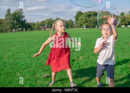 Russland, Moskau - August 24, 2019. Kinder start Seifenblasen, laufen rund um den grünen Bereich, glücklich liebend - Stockfoto