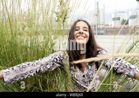 Glückliche Frau zwischen Natur Gras in der Stadt - Stockfoto