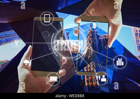 """""""Fintech' Wort auf digitalen virtuellen Bildschirm mit zwei Geschäftsmann Hände halten smartphones Hintergrund. - Stockfoto"""
