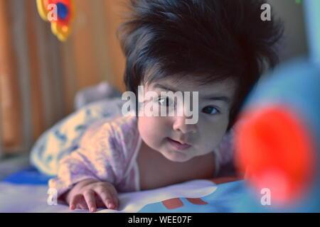 Süße Mischlinge baby girl elegant in die Kamera schaut unter ihrem Spielzeug im Kindergarten - Stockfoto