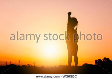 Silhouetten von kleinen Mädchen spielen bei Sonnenuntergang Abend Himmel Hintergrund. - Stockfoto
