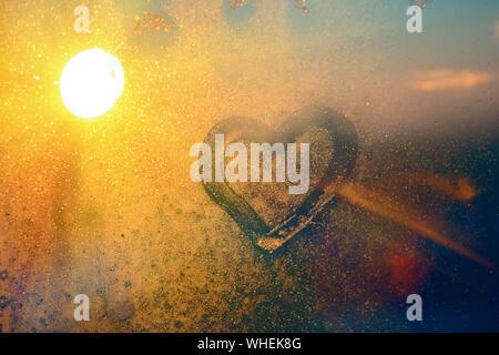 Atemberaubende vintage Orange sunrise Licht mit Herz Liebe Inschrift auf gefrorenen Fenster Glas. Soft Focus. Hintergrund mit kopieren. - Stockfoto