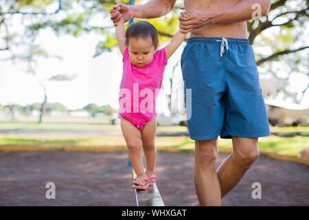 Babys lernen, wie man im Fitnessbereich im Freien Park spazieren zu gehen. Eltern, die Kindern. Meilensteine. - Stockfoto
