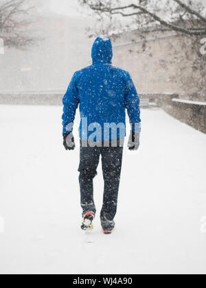 Rückansicht der Mann mittleren Alters wearning blau Outdoor Jacke mit Kapuze, Handschuhe, Jeans und Turnschuhe Wandern im Schnee in einer Stadt in Bayern, Sout - Stockfoto