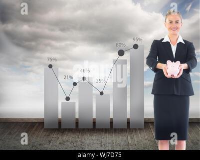 Zusammengesetztes Bild glücklich blonde Geschäftsfrau hält ein rosa Sparschwein - Stockfoto