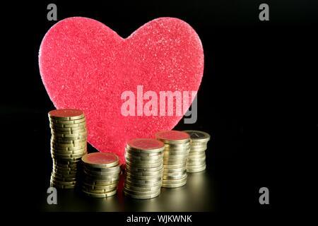 Liebe und Geld Metapher. Valentines candy Herz und Euro-Münzen - Stockfoto