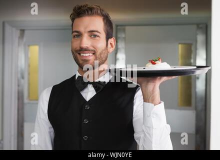 Lächelnd Kellner holding Fach mit Teller von Dessert in einem ausgefallenen Restaurant - Stockfoto