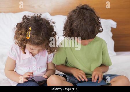 Jungen und Mädchen mit digitalen Tablet-PC und Handy in Bett zu Hause - Stockfoto