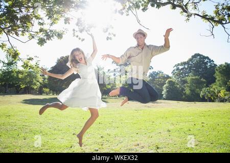 Nettes Paar im Park zusammen Springen an einem sonnigen Tag - Stockfoto