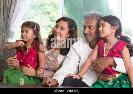 Asiatische indische Familie suchen, um zu Hause Seite. Eltern und Kinder indoor Lifestyle. - Stockfoto