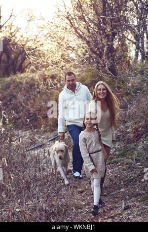 Familie mit 7 Jahre alten Tochter Wandern mit Hund im Herbst - Stockfoto