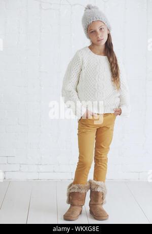 Nettes junges Mädchen 8-9 Jahre alt tragen Knit trendige Winter Kleidung über weiße Mauer posing - Stockfoto