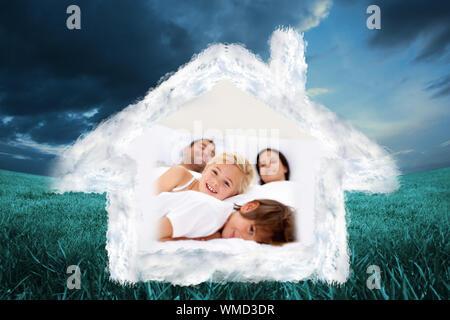 Familie Relaxen im Bett der Eltern gegen den blauen Himmel über grüne Feld - Stockfoto
