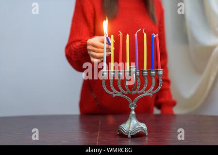 Jüdische Frau Beleuchtung Hanukkah Kerzen in einem MENORAH. Die Menschen feiern Chanukka durch Beleuchtung Kerzen auf der Menora, auch als Hanukiyah. Jede Nacht, eine weitere Kerze angezündet wird. - Stockfoto