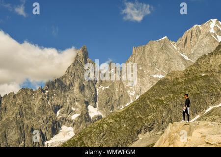 Junger Mann auf einem Felsen mit Blick auf das Mont Blanc Massiv mit der Aiguille Noire de Peuterey Berg im Sommer, Courmayeur, Italien stehend - Stockfoto