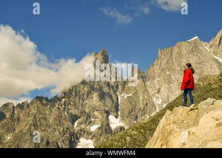 Junge Frau auf einem Felsen mit Blick auf das Mont Blanc Massiv mit der Aiguille Noire de Peuterey Berg, Courmayeur, Aostatal, Italien stehend - Stockfoto