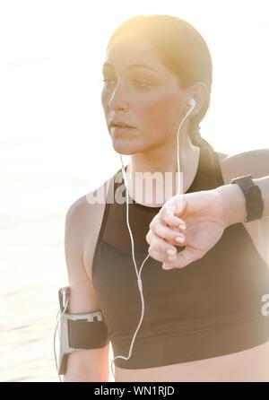 Frau mit Kopfhörern prüfen Armbanduhr am Strand - Stockfoto