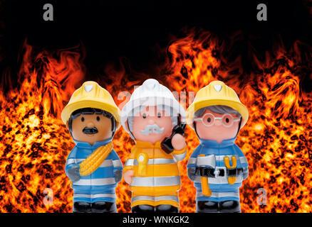 Eine Linie von 3 Spielzeug Feuerwehrmänner ständigen Aufmerksamkeit, mit Flammen brennen im Hintergrund - Stockfoto