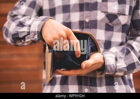 Person, die ein open wallet, auf der Suche nach Bargeld, Armen und Geldlosen Konzepte - Stockfoto