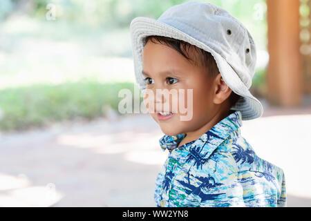 Ein kleines Kind; 3 Jahr alt, mit Hut und Hawaiian Shirt drucken, in die Ferne schauen, mit einem netten Lächeln auf dem Gesicht. - Stockfoto