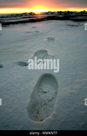 Footprint auf weißem Schnee Männer gehen zu Sun - Stockfoto
