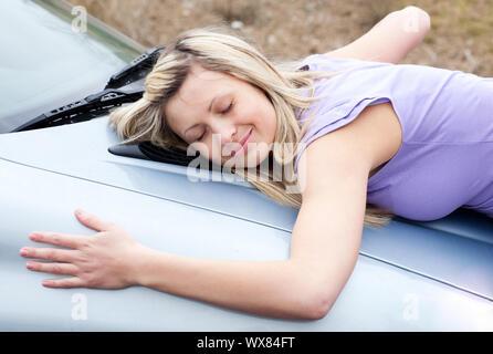 Fröhlicher junger weiblicher Treiber huging Ihr neues Auto - Stockfoto