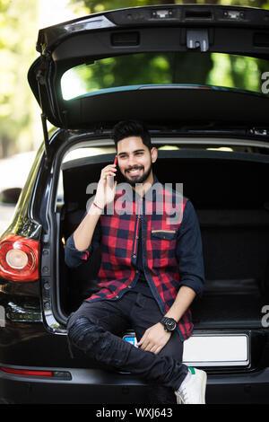 Junge Inder, am Telefon zu sprechen, während im Kofferraum seines Autos sitzen - Stockfoto