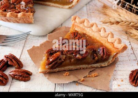 Scheibe der süßen Pecan Pie. Close up Tisch Szene mit einem weißen Holz Hintergrund. - Stockfoto