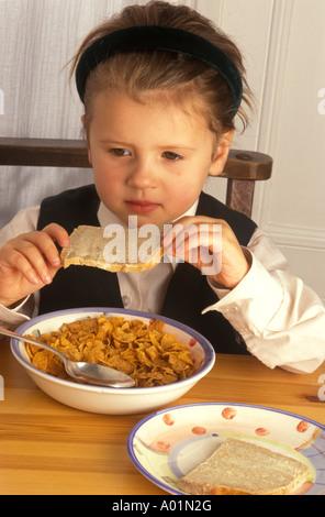 kleine Mädchen essen Frühstück vor der Schule - Stockfoto