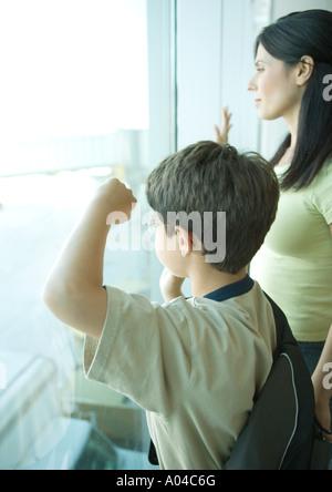 Junge und Mutter Blick durch Fenster am Flughafen - Stockfoto
