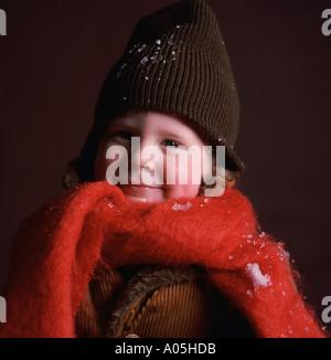 Nahaufnahme eines jungen tragen eine Wintermütze und einen großen roten Schal mit einige Schneeflocken auf ihn - Stockfoto
