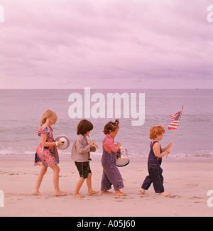Patriotische Bild von ein paar Jungs und Mädchen marschieren entlang des Strandes eine amerikanische Flagge winken - Stockfoto