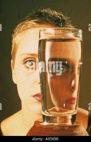 Nahaufnahme einer Frau Fläche wird durch ein Glas Wasser gebrochen - Stockfoto