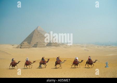 Eine Kamel-Karawane kreuzt vor den Pyramiden von Gizeh in der Nähe von Kairo - Stockfoto