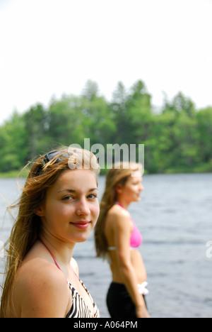 Teenager-Mädchen Blick in die Kamera mit Schwester im Hintergrund in der Hütte - Stockfoto