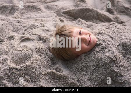 Sechs Jahre alte behaarte Blondschopf im Sand begraben - Stockfoto