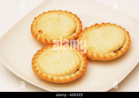 Nahaufnahme von 3 drei traditionelle Mince Pies auf einem weißen Teller, traditionelle saisonale festliche Weihnachten - Stockfoto