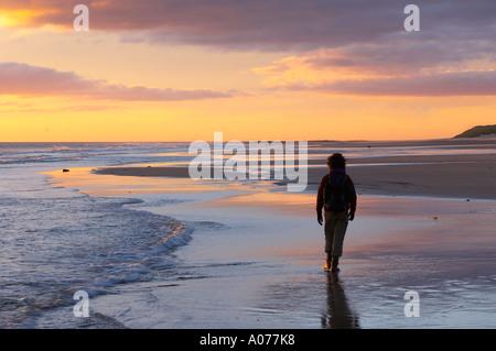 Frau am Strand zu Fuß in der Morgendämmerung Bamburgh Northumbia England UK - Stockfoto