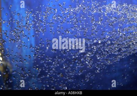 Spritzwasser vor blauem Hintergrund - Stockfoto