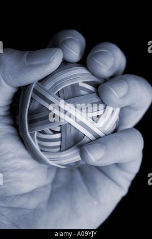 Hand hält einen Gummiband-Ball, zu quetschen, Stress am Arbeitsplatz. - Stockfoto