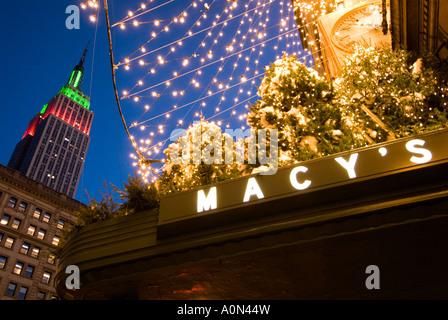Macy s Kaufhaus Zeichen während der Weihnachtszeit mit Blick auf das Empire State Gebäude Midtown Manhattan New - Stockfoto