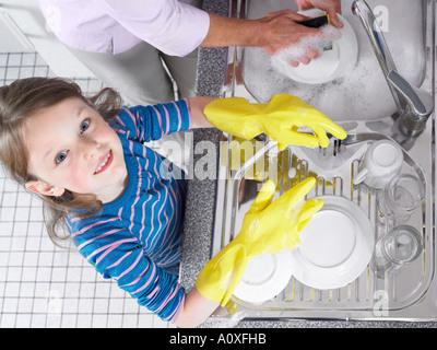 Mädchen mit Abwasch helfen - Stockfoto
