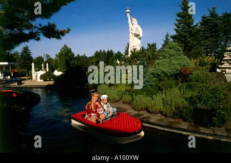 Mutter und Kind genießen Sie eine Fahrt auf einem Lego Mini Boot auf einem von Bäumen gesäumten Fluss in Billund - Stockfoto