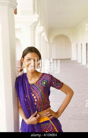 Porträt einer jungen Frau an eine Säule gelehnt und lächelnd, Agra, Uttar Pradesh, Indien - Stockfoto